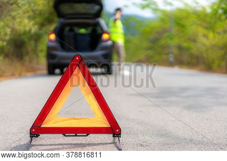 Breakdown Triangle Sign On Road With Worried Asian Man Talking By Mobile Phone With Insurance Or Car