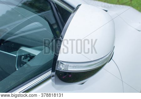 Cars Run Through The Street From The White Car's Side View Mirror. City Beside. Road Car Rear View M