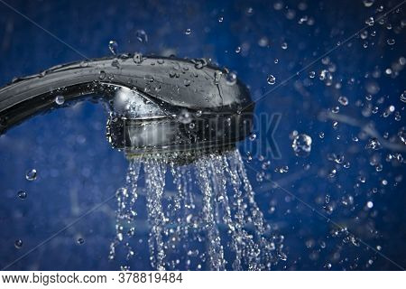 Shower Head Against Blue Wall Of Bathroom With Water Drops Flying By.