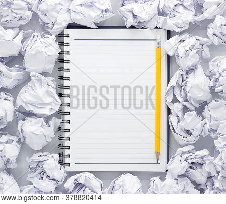 White Note Pad On White Background. Around The Notepads Lies Lot Crumpled Paper,copy Space