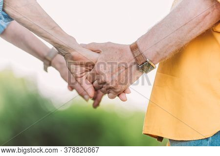 Cropped View Of Senior Man In Wristwatch And Woman Holding Hands Outdoors