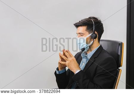 Man In Suit Sitting At A Desk And Clasp His Hand, Young Operator Man With Headset Wear Protection Fa
