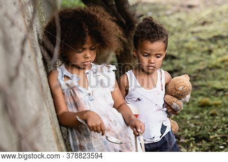 Selective Focus Of Helpless African American Kids With Spoon, Cup And Teddy Bear Standing Near Concr