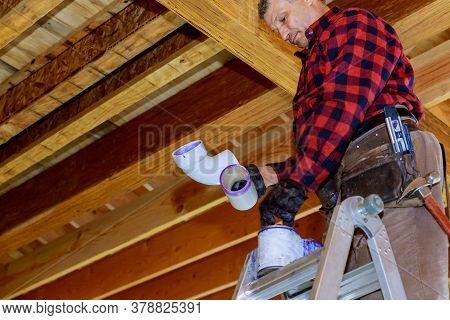 Plumber Gluing Pvc Plastic Sewer Toilet White Pipe On Wooden Frame Ceiling Beam Of House Soft Focus