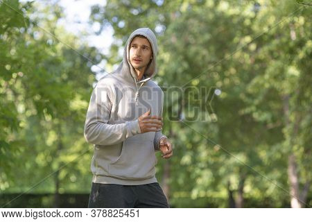 Sportsman Runs Along The Road In The Forest. The Concept Of Sport And A Healthy Lifestyle.