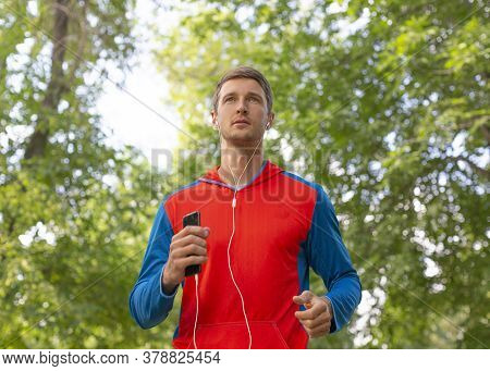Sportsman Runs Along The Road In The Forest. He Listening To The Music Via Earphones. The Concept Of