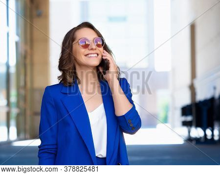 Smiley Businesswoman In Sunglasses And Blue Suit Walking In A Business District Of A City And Talkin