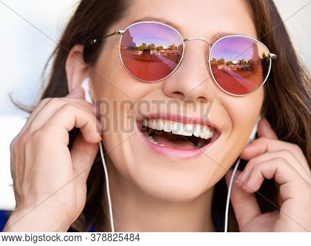 Happy Smiling Woman In Sunglasses With Earphones. Close-up Portrait.