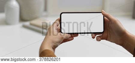 Hands Holding Horizontal Smartphone With Clipping Path At Workspace