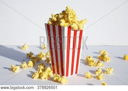 Popcorn. Popcorn in a White and Red Striped Container. On a White Background. Popcorn Text. Popcorn is enjoyed world wide by happy people and animals alike. Room for text. Clipping Path.