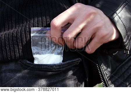 A Man Takes Out A Plastic Bag From A Jeans Pocket With A Dose Of Cocaine Or Another Concept Of Drugs