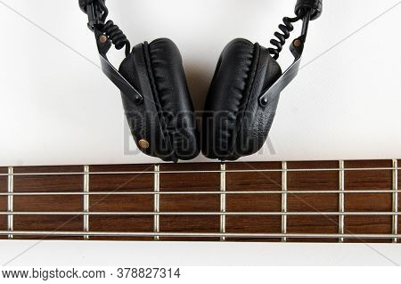Portable Black Headphones And Fretboard From Bass Guitar On White Background. Layout, Creative Desig