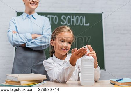 Partial View Of Teacher Standing With Crossed Arms Near Schoolgirl Applying Antiseptic On Hands