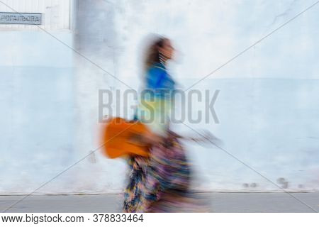 Young Female Musician Walking With Guitar On City Street. Intentional Camera Shake To Introduce An I