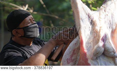 Yogyakarta, Indonesia - July 31, 2020: Eid Al-adha Celebration. Muslim People Using Mask Help Each O