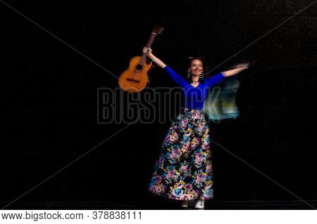 Carefree Happy Musician Dancing With Guitar On Black Background. Long Exposure, To Introduce An Impr