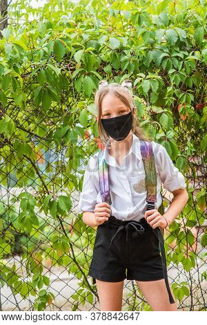 Schoolgirl Girl In A Black Protective Mask With A Backpack. Schoolgirl In A White Shirt And Black Sh