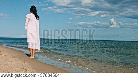 Woman standing on the empty beach on sunny day.