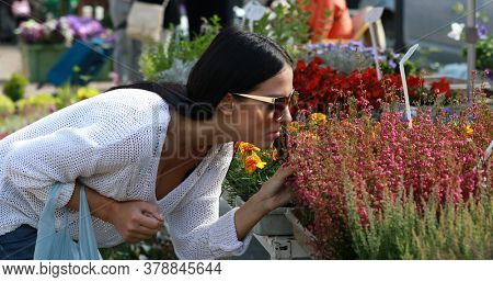 Woman at city market smelling flowers