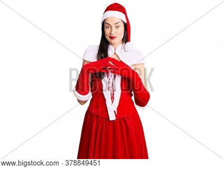 Young beautiful caucasian woman wearing santa claus costume hands together and fingers crossed smiling relaxed and cheerful. success and optimistic