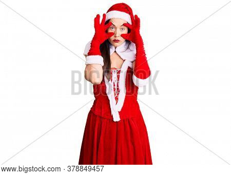 Young beautiful caucasian woman wearing santa claus costume trying to open eyes with fingers, sleepy and tired for morning fatigue