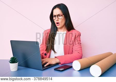 Young caucasian woman sitting at the desk working using laptop and architect blueprints scared and amazed with open mouth for surprise, disbelief face