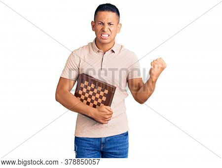 Young handsome latin man holding chess annoyed and frustrated shouting with anger, yelling crazy with anger and hand raised
