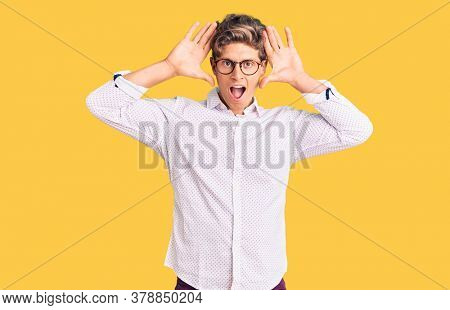 Young handsome man wearing business clothes and glasses smiling cheerful playing peek a boo with hands showing face. surprised and exited
