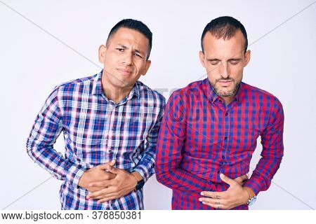 Young gay couple of two men wearing casual clothes with hand on stomach because indigestion, painful illness feeling unwell. ache concept.