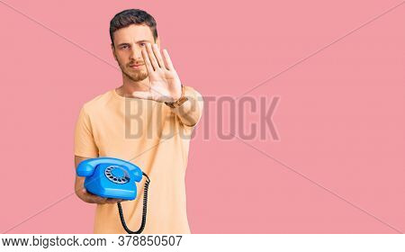 Handsome young man with bear holding vintage telephone with open hand doing stop sign with serious and confident expression, defense gesture