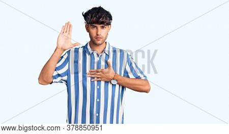 Young hispanic man wearing casual clothes swearing with hand on chest and open palm, making a loyalty promise oath