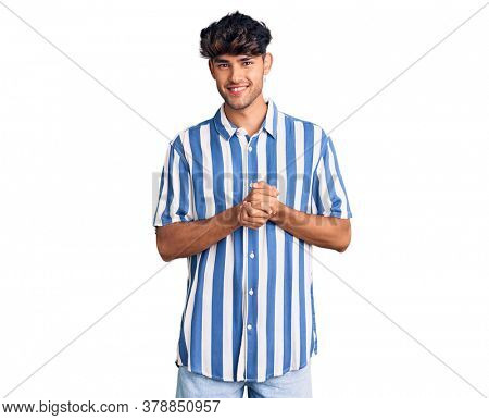 Young hispanic man wearing casual clothes with hands together and crossed fingers smiling relaxed and cheerful. success and optimistic