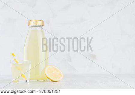 Fresh Yellow Lemon Juice In Glass Bottle Mock Up With Straw, Wine Glass, Fruit Slice On White Wood T