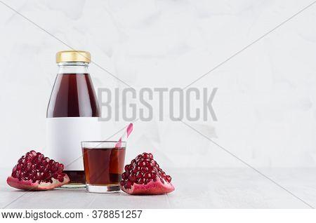 Fresh Red Garnet Juice In Glass Bottle Mock Up With Blank Label, Straw, Wine Glass, Fruit Piece On W