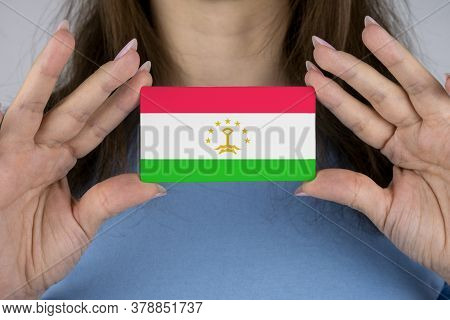 A Woman Shows A Business Card With An Image Of The Tajikistan Flag.
