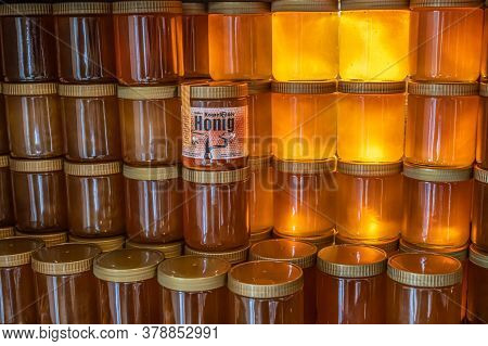 Koblenz Germany 14.06.2020 Tower And Rows Of Golden Yellow Honey In Glass Jar On Wooden Board Closeu