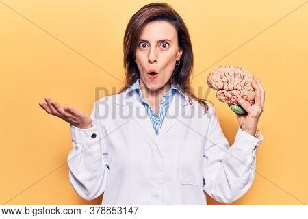 Young beautiful woman wearing doctor coat holding brain scared and amazed with open mouth for surprise, disbelief face