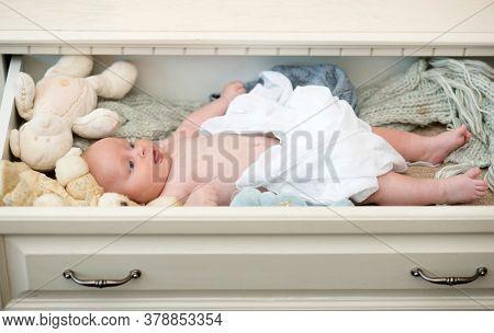 Infant Covered With White Duvet Near Toys