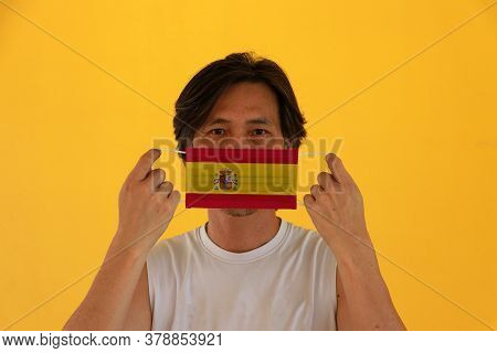 A Man With Spain Flag On Hygienic Mask In His Hand And Lifted Up The Front Face On Yellow Background