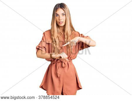 Beautiful caucasian woman with blonde hair wearing summer jumpsuit in hurry pointing to watch time, impatience, upset and angry for deadline delay
