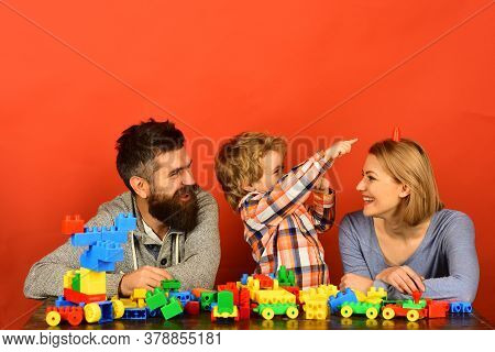 Parents And Kid In Playroom. Family With Cheerful Faces