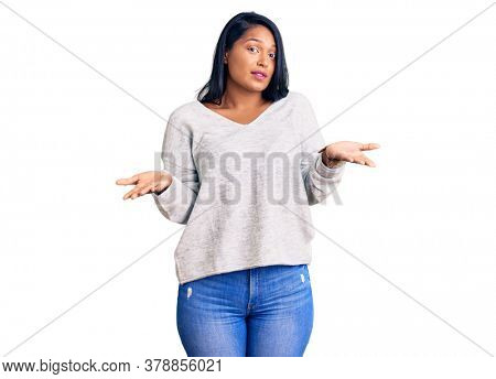 Hispanic woman with long hair wearing casual clothes clueless and confused with open arms, no idea concept.