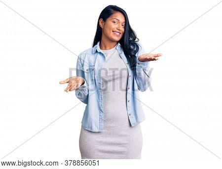 Hispanic woman with long hair wearing casual denim jacket clueless and confused expression with arms and hands raised. doubt concept.