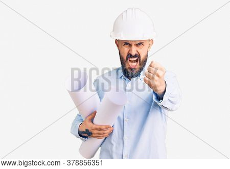 Young handsome man wearing hardhat holding paper blueprints annoyed and frustrated shouting with anger, yelling crazy with anger and hand raised
