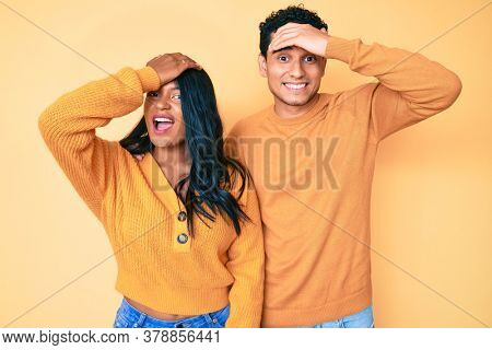 Beautiful latin young couple wearing casual clothes together surprised with hand on head for mistake, remember error. forgot, bad memory concept.