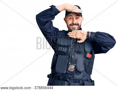 Young handsome man wearing police uniform smiling cheerful playing peek a boo with hands showing face. surprised and exited