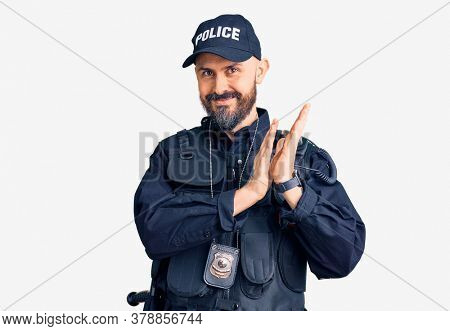 Young handsome man wearing police uniform clapping and applauding happy and joyful, smiling proud hands together