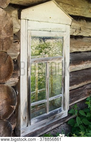 Wooden Window In An Old Log House. The Paint Exfoliated, Worn Away From Time. Reflection In The Glas