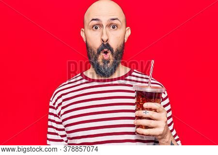Young handsome man drinking glass of cola beverage scared and amazed with open mouth for surprise, disbelief face