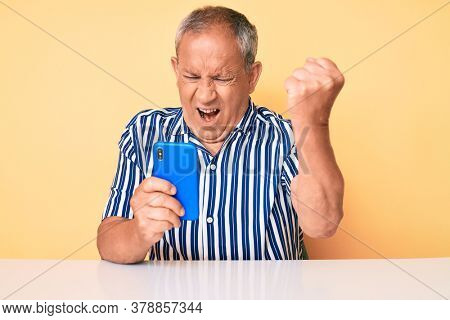Senior handsome man with gray hair using smartphone sitting on the table annoyed and frustrated shouting with anger, yelling crazy with anger and hand raised